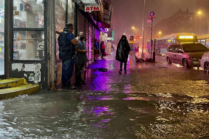 People work their way through precipitation from the remnants of Hurricane Ida on September 1, 2021, in the Bronx neighborhood of New York City.