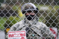 A member of the Washington National Guard stands at a fence surrounding the Capitol in anticipation of protests Monday, Jan. 11, 2021, in Olympia, Wash. State capitols across the country are under heightened security after the siege of the U.S. Capitol last week. (AP Photo/Ted S. Warren)