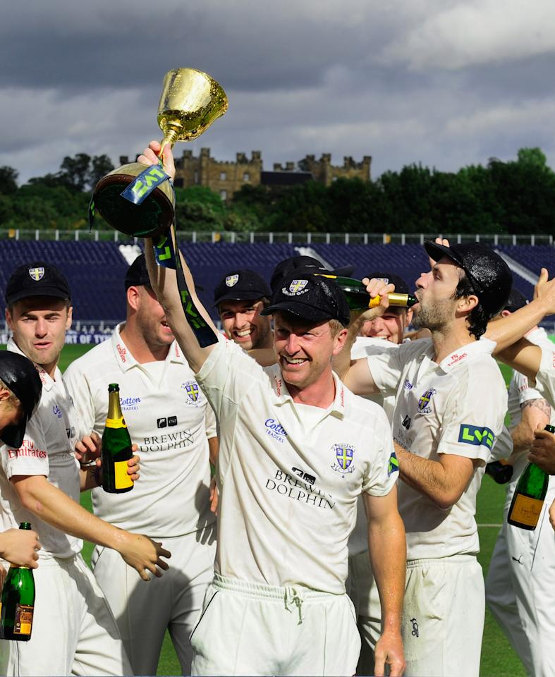 CHESTER-LE-STREET, ENGLAND - SEPTEMBER 19:  Durham captain Paul Collingwood (c) and team celebrate with the trophy after winning the LV County Championship Division One title after day three of the LV County Championship Division One match between Durham and Nottinghamshire at The Riverside on September 19, 2013 in Chester-le-Street, England.  (Photo by Stu Forster/Getty Images)