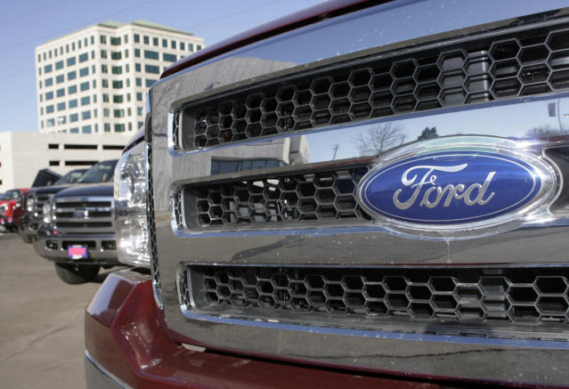 The company logo shines off the grille of an unsold 2007 F350 pickup truck in a long line of unsold pickups on the lot of a Ford dealership in Denver on Sunday, Dec. 10, 2006. (AP Photo/David Zalubowski)