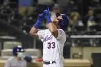 New York Mets' James McCann (33) gestures as he reaches home plate after hitting a two-run home run during the eighth inning of a baseball game against the Philadelphia Phillies Wednesday, April 14, 2021, in New York. (AP Photo/Frank Franklin II)