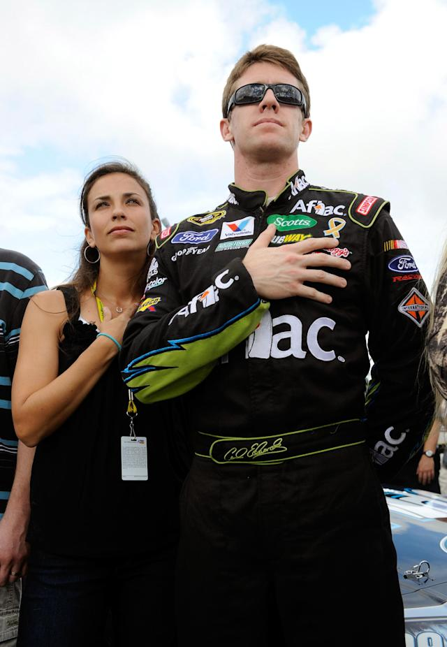 HOMESTEAD, FL - NOVEMBER 20: Carl Edwards, driver of the #99 Aflac Ford, and wife Kate Edwards cover their heart during the singing of the national anthem as they stand next to his car on the grid before the NASCAR Sprint Cup Series Ford 400 at Homestead-Miami Speedway on November 20, 2011 in Homestead, Florida. (Photo by Jared C. Tilton/Getty Images)
