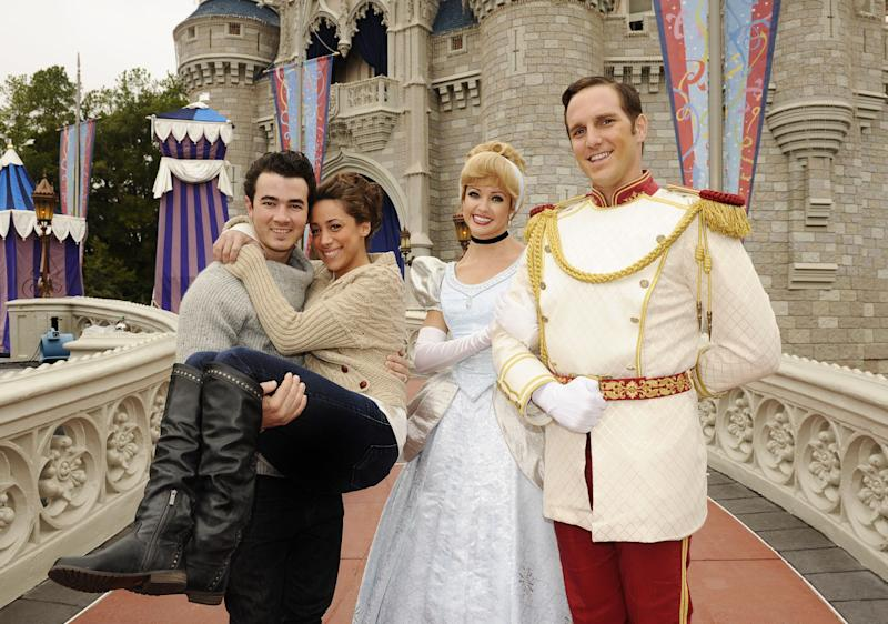 Kevin Jonas and his wife at Disney World alongside Disney characters