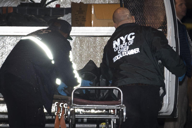 Medical Examiner Transport personnel place a loaded body bag into their vehicle Sunday, Oct. 27, 2013 after exiting the residence of a crime scene in the Sunset Park neighborhood of Brooklyn where five people, including a toddler, were stabbed to death earlier in New York. Emergency responders found three of the victims dead at the residence just before 11 p.m. Saturday. Two others were taken to Brooklyn hospitals, where they were pronounced dead. (AP Photo/John Minchillo)