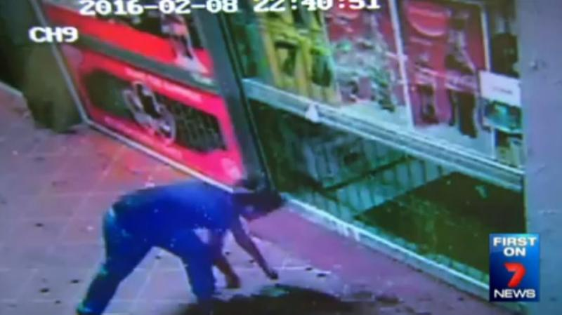The 19-year-old throws bricks repeatedly into the window of the shops. Photo: 7 News