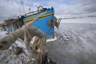 Ice builds up and boats are stuck in the marina of Monnickendam, Netherlands, Tuesday, Feb. 9, 2021. With freezing temperatures forecast for more than a week in the Netherlands, ice fever is sweeping the nation, offering a welcome respite from grim coronavirus news while also creating a challenge for authorities trying to uphold social distancing measures. (AP Photo/Peter Dejong)