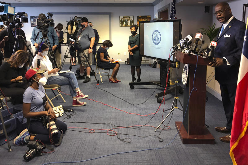 Atlanta Journal-Constitution staff photojournalist Alyssa Pointer, left, works during a news conference, Tuesday, June 2, 2020, in Atlanta. Pointer was detained by officers of the Georgia Department of Natural Resources during a protest in downtown. Pointer said her press badge was clearly displayed, and she identified herself to law enforcement. (AP Photo/Kate Brumback)