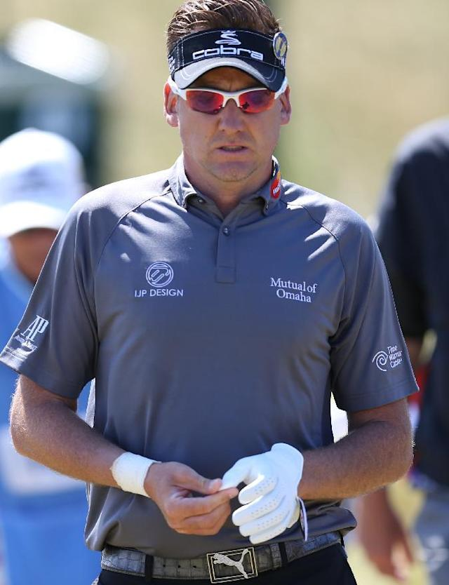 Ian Poulter of England takes off his glove after playing a shot off the 7th tee during a practice round ahead of the British Open Golf championship at the Royal Liverpool golf club, Hoylake, England, Tuesday July 15, 2014. The British Open Golf championship starts on Thursday July 17. (AP Photo/Scott Heppell)