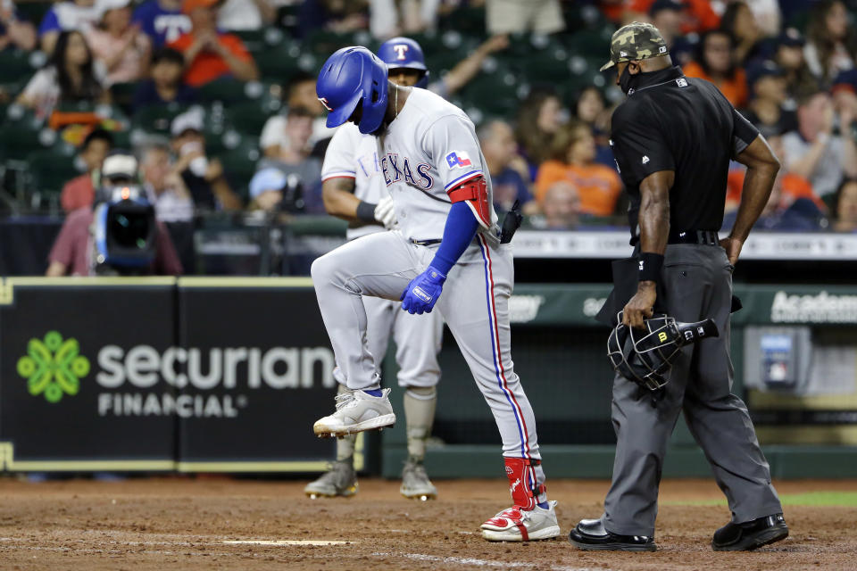 Texas Rangers' Adolis Garcia, left, stomps on home plate next to umpire Alan Porter, right, after his home against the Houston Astros during the eighth inning of a baseball game Friday, May 14, 2021, in Houston. (AP Photo/Michael Wyke)