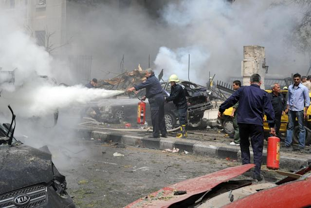 This photo released by the Syrian official news agency SANA, shows Syrian fire fighters extinguishing burning cars after a huge explosion shook the Sabaa Bahrat Square, one of the capital's biggest roundabouts, in Damascus, Syria, Monday, April. 8, 2013. A car bomb rocked a busy residential and commercial district in central Damascus, killing over a dozen people, wounding at least 50 and causing heavy material damage, a Syrian government official said. (AP Photo/SANA)