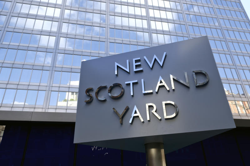 """London, United Kingdom - September 22, 2012: New Scotland Yard, London. Iconic rotating sign outside New Scotland Yard, headquarters of the Metropolitan Police who are responsible for policing Greater London. The sign, which is a tourist attraction, has recently been moved as it was causing congestion at the main entrance to the building."""