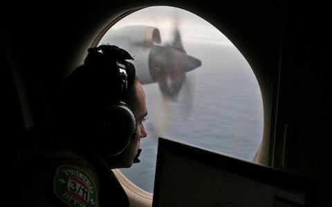 <span>Rayan Gharazeddine scans the water in the southern Indian Ocean off Australia from a Royal Australian Air Force AP-3C Orion during a search for the missing plane in 2014</span> <span>Credit: Rob Griffith/AP </span>