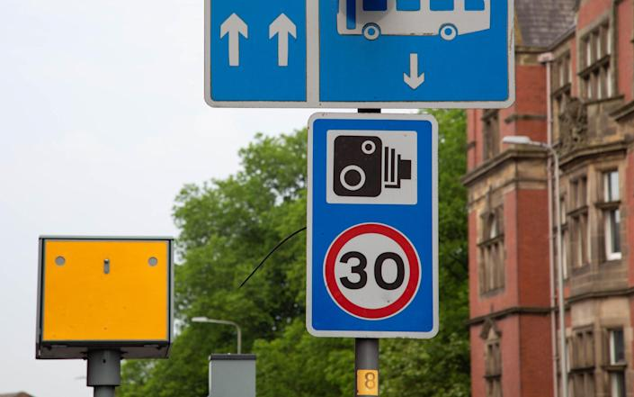 Street signs indicating the presence of bus lanes speed limits and speed cameras - Graeme Lamb/Alamy