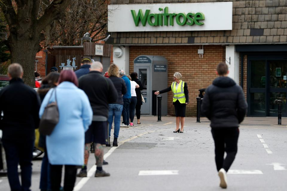 "A member of staff enforces social distancing rules in a queue outside a Waitrose supermarket in Frimley, south west of London on March 29, 2020, as life in Britain continues during the nationwide lockdown to combat the novel coronavirus pandemic. - Prime Minister Boris Johnson warned Saturday the coronavirus outbreak will get worse before it gets better, as the number of deaths in Britain rose 260 in one day to over 1,000. The Conservative leader, who himself tested positive for COVID-19 this week, issued the warning in a leaflet being sent to all UK households explaining how their actions can help limit the spread. ""We know things will get worse before they get better,"" Johnson wrote. (Photo by Adrian DENNIS / AFP) (Photo by ADRIAN DENNIS/AFP via Getty Images)"