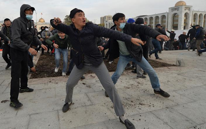 Supporters of nationalist Sadyr Japarov throw clumps of earth towards supporters of former Kyrgyzstan's President Almazbek Atambayev as they attend a rally in Bishkek - VYACHESLAV OSELEDKO /AFP