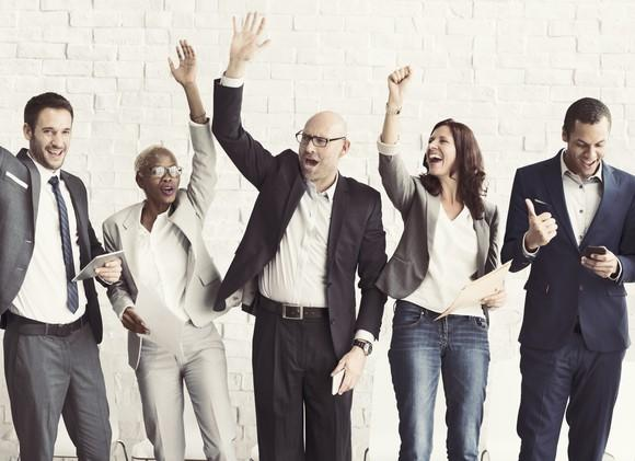 A group of people in business attire, being enthusiastic.