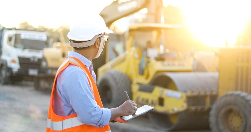 A man in a hard hat and safety vest holds a tablet computer as he looks at a group of construction vehicles.
