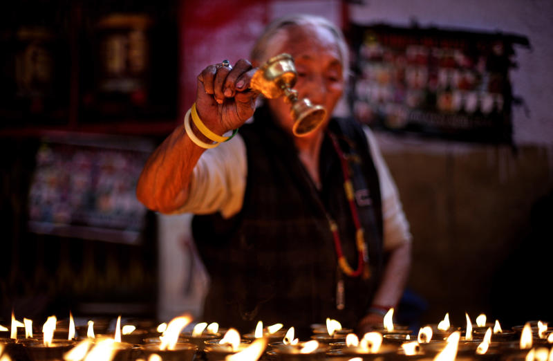 An elderly exile Tibetan arranges butter lamps during a special prayer session for Tibetan Jampa Yeshi who immolated himself Monday during a protest, at a Tibetan Refugee settlement in New Delhi, India, Tuesday, March 27, 2012. Yeshi, who remains in critical condition, set himself on fire and ran shouting through a protest in the Indian capital Monday, just ahead of a visit by China's president Hu Jintao for an economic summit this week. (AP Photo/Altaf Qadri)