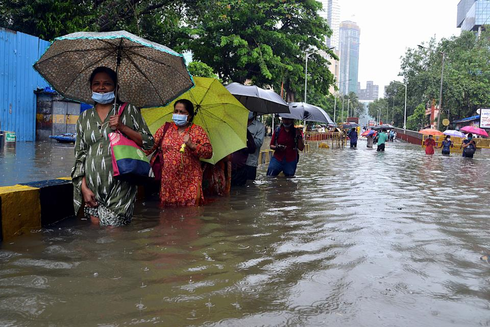 People wade in knee deep water along a flooded road during a heavy monsoon rainfall in Mumbai on August 4, 2020 (Photo by Sujit Jaiswal / AFP) (Photo by SUJIT JAISWAL/AFP via Getty Images)