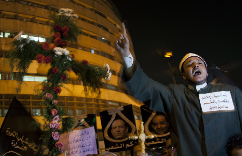 """An Egyptian Muslim cleric chants anti-Muslim Brotherhood slogans as he stands next to a cross made of flowers during a march marking the first anniversary of the victims who were killed during clashes with the military police in front of the National State T.V. building, known as Maspero, in Cairo, Egypt, Tuesday, Oct. 9, 2012. Muslim clerics, Christian priests, activists and former liberal lawmakers were among those marching to mark the anniversary of the """"Maspero massacre,"""" referring to the name of the state TV building, where the clashes broke out. (AP Photo/Khalil Hamra)"""
