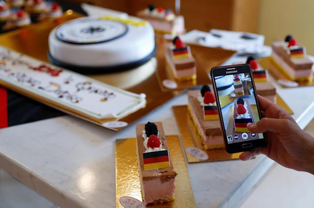 A tourist takes a picture of a tartlets with the German flag in a pastry shop in Eppan, Italy May 24, 2018. REUTERS/Leonhard Foeger