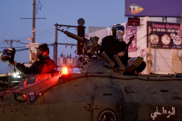 Members of Tunisia's National Guard sit atop an armoured personnel carrier to stop protesters