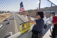 Volunteers wave flags and hold recall Gov. Gavin Newsom signs along the I-14 freeway at Golden Valley road in Santa Clarita, Calif., Monday, Sept. 13, 2021. Voting concludes Tuesday in California's recall election. (David Crane/The Orange County Register via AP)