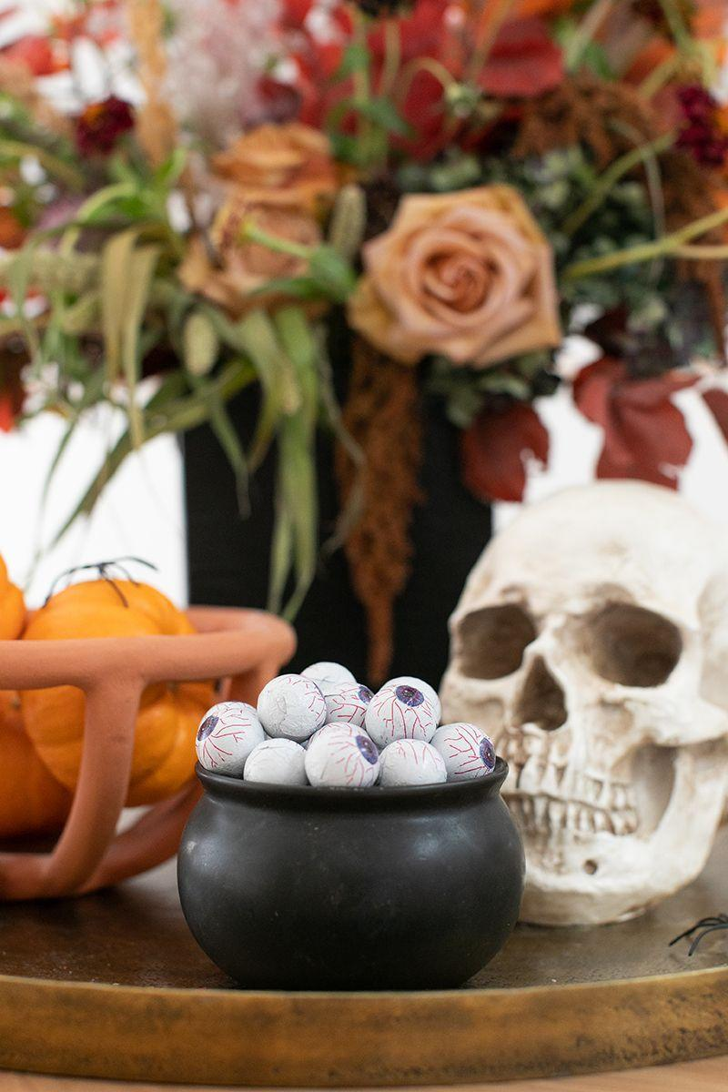 "<p>Use a small black bowl to pose as a mini cauldron and fill it with edible ""eyeballs,"" aka chocolates wrapped in bloodshot eye motif foil, as seen in this Halloween spread styled by <a href=""https://sugarandcharm.com/inexpensive-halloween-decorating-ideas"" rel=""nofollow noopener"" target=""_blank"" data-ylk=""slk:Sugar & Charm"" class=""link rapid-noclick-resp"">Sugar & Charm</a>. Or, if you can't find those, glue googly eyes to the candy wrappers</p><p><a class=""link rapid-noclick-resp"" href=""https://www.candywarehouse.com/googly-eyes-foiled-double-crisp-chocolate-eyeballs-2lb-bag"" rel=""nofollow noopener"" target=""_blank"" data-ylk=""slk:BUY NOW"">BUY NOW</a><strong><em> Eyeball Chocolates, $14</em></strong></p>"