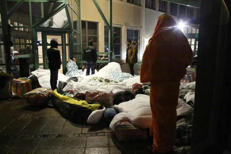 Migrants sleep outside the entrance of the Swedish migration agency's arrival centre in Malmo