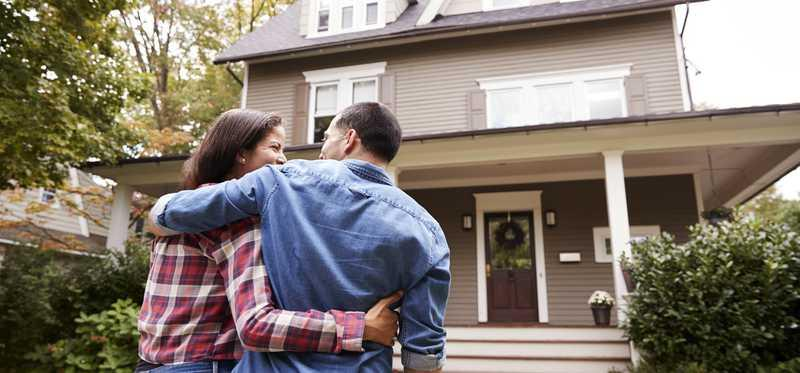 A couple hugs one another in front of a house.