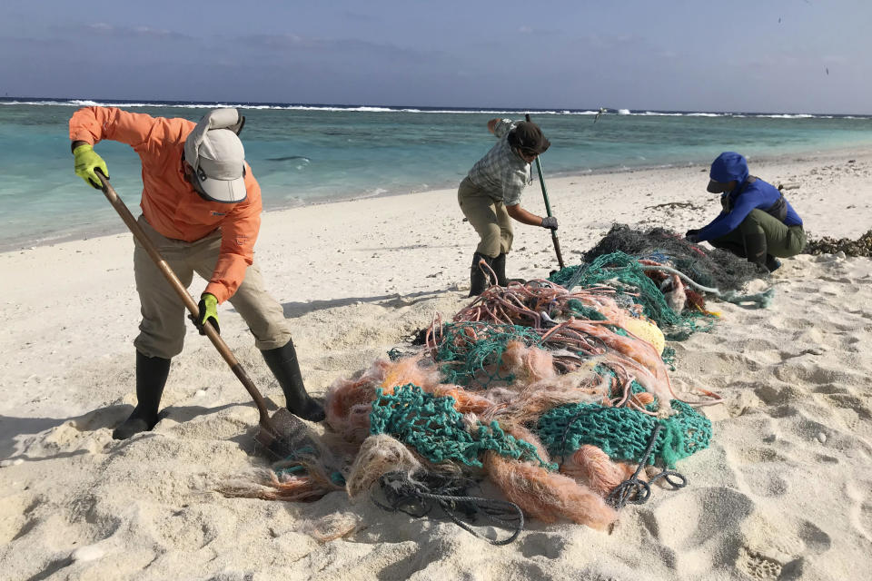 In this March 12, 2020, photo provided by Matt Saunter, Matt Butschek II, left, Charlie Thomas, center, and Naomi Worcester clean up fishing nets at a field camp on Kure Atoll in the Northwestern Hawaiian Islands. Cut off from the rest of the planet since February, the environmental field workers are back, re-emerging into a society changed by the coronavirus outbreak. (Matt Saunter/Hawaii Department of Land and Natural Resources via AP)