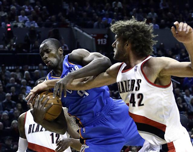 Oklahoma City Thunder forward Serge Ibaka, left, from the Republic of Congo, battles for the ball with Portland Trail Blazers center Robin Lopez during the first half of an NBA basketball game in Portland, Ore., Wednesday, Dec. 4, 2013. (AP Photo/Don Ryan)