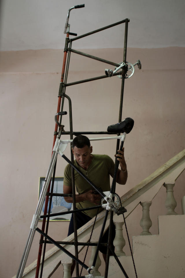 In this June 1, 2012 photo, Felix Guirola accommodates one of his bicycles at his house in Havana, Cuba. Guirola has been riding tall since 1983, when seeing a tandem bike inspired him to build up instead of out. He said his first tall bike measured 5.3 feet (1.6 meters), and they got progressively taller until five years later he was riding 18 feet (5.5 meters) in the air at Ciego de Avila carnivals. (AP Photo/Franklin Reyes)