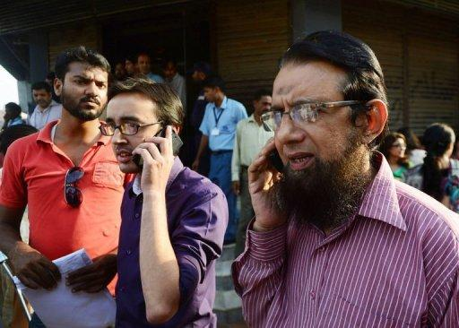<p>Pakistani office workers speak on their mobile phones after an earthquake in Karachi on September 24, 2013. The death toll from the quake that struck a remote part of southwestern Pakistan jumped to at least 208 on Wednesday.</p>