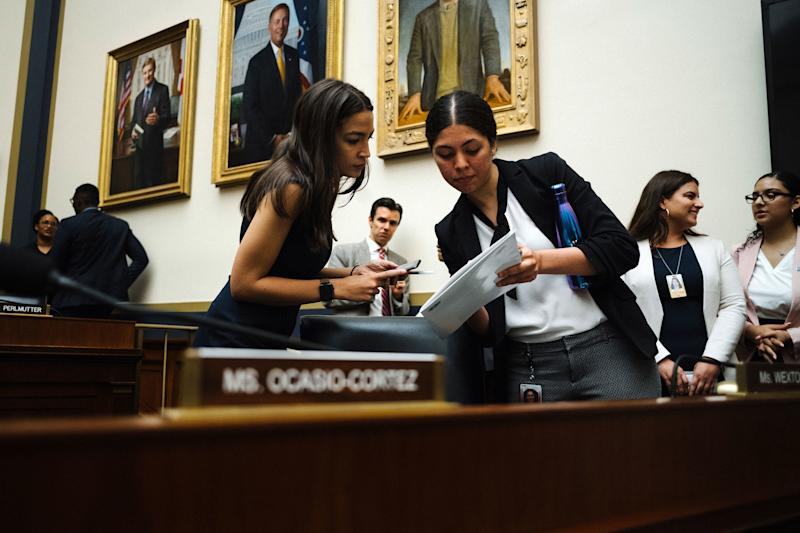 Ocasio-Cortez views information with her staff assistant Claudia Pagon Marchena, 22, before a hearing in front of the Financial Services Committee.