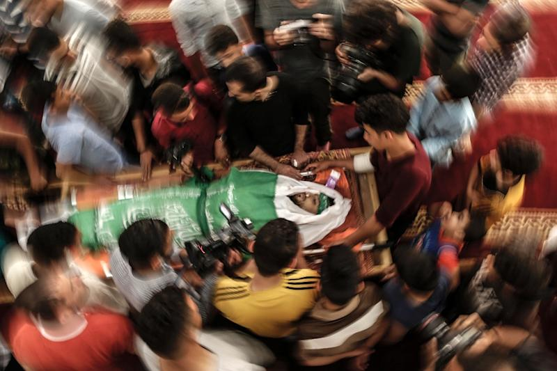 Palestinian mourners in Gaza City pictured on May 15, 2018 surrounding the body of Yazan Tubasi, killed during clashes in Gaza the previous day (AFP Photo/MAHMUD HAMS)