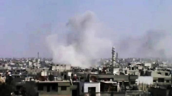 In this image made from amateur video released by the Syrian Media Council and accessed Tuesday, April 10, 2012, smoke rises following purported shelling in Homs, Syria. Syrian troops shelled and raided opposition strongholds across Syria on Tuesday, activists said, denying claims by the foreign minister that regime forces have begun pulling out of some areas in compliance with a U.N.-brokered truce. (AP Photo/Syrian Media Council via AP video) TV OUT, THE ASSOCIATED PRESS CANNOT INDEPENDENTLY VERIFY THE CONTENT, DATE, LOCATION OR AUTHENTICITY OF THIS MATERIAL