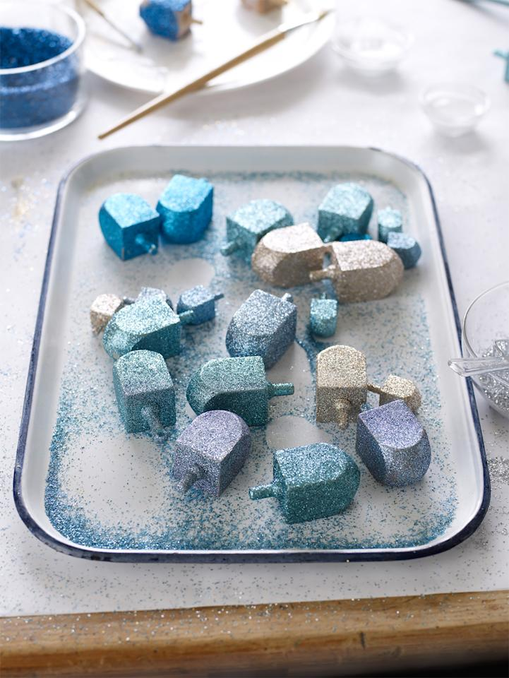 """<p>A coating of fine glitter turns plain wooden dreidels <a href=""""https://www.marthastewart.com/1523962/hanukkah-party-with-latke-bar"""">into a display-worthy centerpiece</a>. You could also string them together to create a shimmering garland. To make the centerpiece and the garland, we used plain wooden dreidels, in varying sizes, and different shades of glitter with a fine coating of adhesive. Even the smallest of children can handle dipping their dreidels in the glitter color they like best.</p>"""