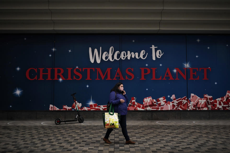 A woman, wearing a face mask to prevent the spread of the coronavirus, walks past a board promoting Christmas shopping in a commercial street in downtown Brussels, Tuesday, Dec. 1, 2020. Non-essential shops in Belgium are reopening on Tuesday in the wake of encouraging figures about declining infection rates and hospital admissions because of the coronavirus. (AP Photo/Francisco Seco)