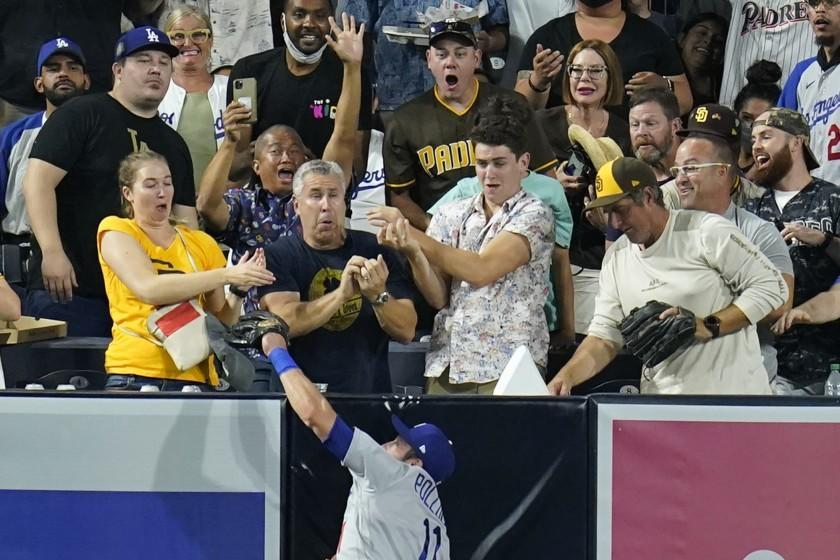 Los Angeles Dodgers left fielder AJ Pollock makes the catch at the wall, competing against fans for the ball, for the out on San Diego Padres' Manny Machado during the fourth inning of a baseball game Tuesday, Aug. 24, 2021, in San Diego. (AP Photo/Gregory Bull)