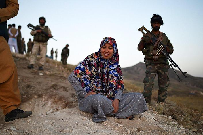 This photograph taken on July 14, 2021 shows Salima Mazari (C), a female district governor in male-dominated Afghanistan, looking on from a hill while accompanied by security personnel near the frontlines against the Taliban at Charkint district in Balkh province. - Mazari, a female district governor in male-dominated Afghanistan, is on a mission -- recruiting menfolk to fight the Taliban.