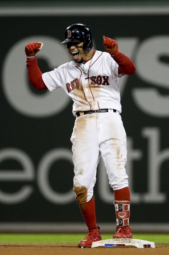 Boston Red Sox's Mookie Betts celebrates after his RBI-double against the Houston Astros during the eighth inning in Game 2 of a baseball American League Championship Series on Sunday, Oct. 14, 2018, in Boston. (AP Photo/David J. Phillip)