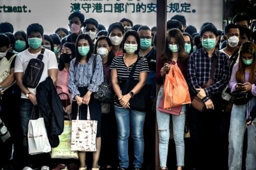 Commuters are shown in Bangkok wearing face masks, which are in short supply across all of Asia