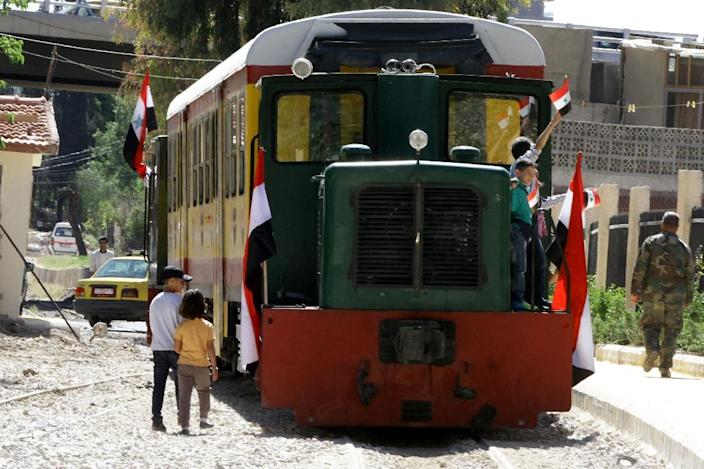 Syrians ride the tourist train bearing the Syrian flag in Damascus, following the re-opening ceremony of the rail route between two neighbourhoods in the Syrian capital, Raboeh and Dumar, on May 1, 2015 (AFP Photo/Louai Beshara)