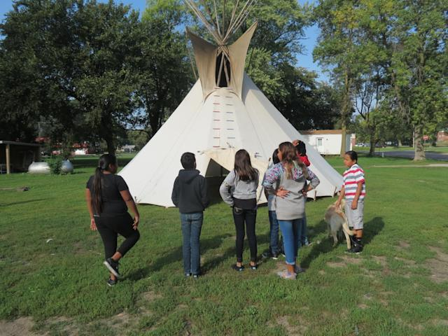 A middle school class from Umonhon Nation Public School, out on a cultural experience in the community, learning about the tipi.