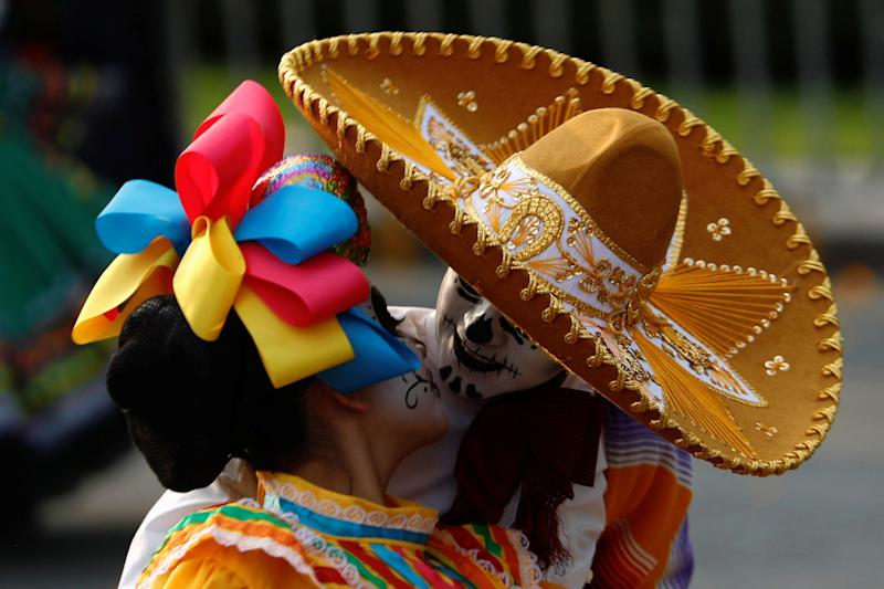 A painted couple kiss during Day of the Day festivities in Mexico City on Saturday.