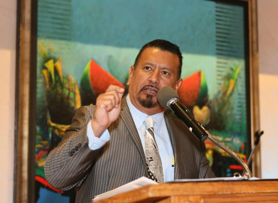 Richard Montañez speaks at a lectern in front of a painting