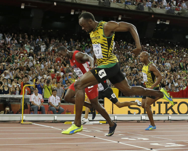 "FILE - In this Aug. 23, 2015, file photo, Jamaica's Usain Bolt crosses the finishing in front of United States' Justin Gatlin, left, to win the men's 100m final at the World Athletics Championships at the Bird's Nest stadium in Beijing. The race that still haunts him? Easy: A premature lean that led to a loss to Bolt in the 100 at the 2015 world championships. On the ride to the hotel, ""I cried every tear I needed to cry from 2006 all the way up to that night,"" Gatlin said in a new documentary titled, ""Rise Again — The Justin Gatlin Story,"" an hour-long film produced by Andrew Brereton. (AP Photo/David J. Phillip, File)"