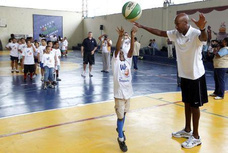 Former NBA player Bruce Bowen (R) plays with children during NBA's Americas Team Camp at Cantagalo slum in Rio de Janeiro September 24. 2010. REUTERS/Bruno Domingos