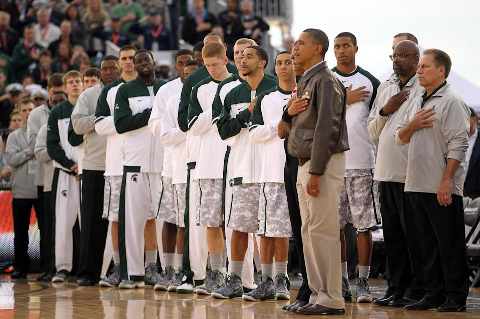 SAN DIEGO, CA - NOVEMBER 11: U.S. President Barack Obama and first lady Michelle Obama stand next to the Michigan State Spartans during the United States National Anthem before the start of the NCAA men's college basketball Carrier Classic between the Spartans and the North Carolina Tar Heels aboard the flight deck of the USS Carl Vinson on November 11, 2011 in San Diego, California. (Photo by Ezra Shaw/Getty Images)